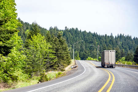 Classic big rig industrial semi truck with semi trailer for for transporting animals running on curving highway road with green mountain forest in Columbia Gorge