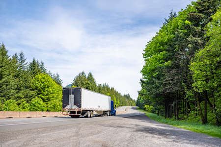 Blue big rig industrial semi truck tractor with roof spoiler transporting cargo in dry van semi trailer with aerodynamic tail on the back running on curving highway road with forest in Columbia Gorge