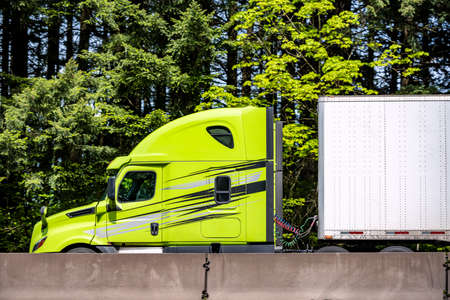 Bright lime big rig long haul industrial semi truck tractor with roof spoiler transporting cargo in dry van semi trailer running on highway road with green forest trees in Columbia Gorge 版權商用圖片