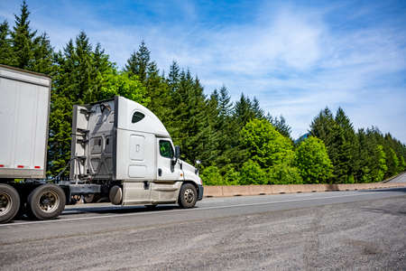 White big rig long haul industrial semi truck tractor transporting cargo in dry van semi trailer running on curving highway road with protective fence and green mountain forest in Columbia Gorge 版權商用圖片