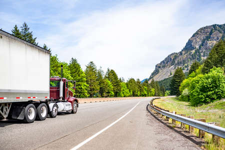 Burgundy day cab big rig industrial semi truck tractor for local deliveries transporting cargo in dry van semi trailer running on highway road with green forest trees in Columbia Gorge