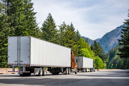 Two big rig industrial semi truck tractors transporting commercial cargo in different semi trailers running side by side at same direction on highway road with green forest trees in Columbia Gorge 版權商用圖片