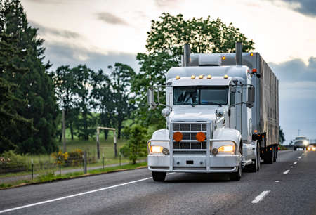 White big rig long haul industrial semi truck with turned on headlight transporting commercial cargo in tented black dry van semi trailer running on the evening highway road at twilight time