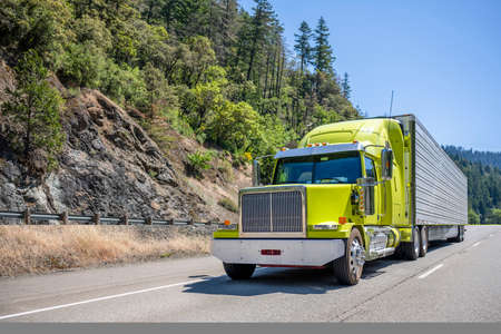 Bright lime stylish industrial grade long haul Big rig bonnet semi truck transporting frozen commercial cargo in refrigerator semi trailer running for delivery on the one way multiline highway road