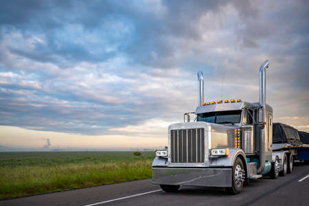 Gray classic big rig American semi truck with turned on lights and chrome exhaust pipes transporting covered cargo on flat bed semi trailer driving on the twilight highway road with stormy clouds sky
