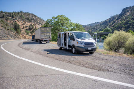 Commercial compact mini van and loaded big rig semi trucks with semi trailers take a break standing on the road shoulder on the bank of a mountain river in California along the highway Stock fotó