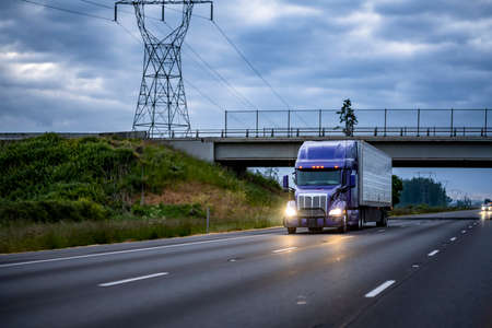 Blue industrial long haul Big rig bonnet semi truck with chrome transporting frozen commercial cargo in refrigerator semi trailer running for delivery on the wide multiline highway road at twilight
