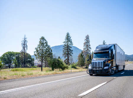 Black big rig long haul industrial semi truck with grille guard transporting commercial cargo in dry van semi trailer running on the one way highway road with trees and mountain on background