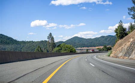 Stylish industrial long haul big rig bonnet semi truck transporting frozen commercial cargo in refrigerator semi trailer running for delivery on the overpass road with bridge across the Shasta Lake