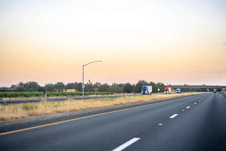 Team of group big rigs industrial professional semi trucks tractors transporting cargo in different semi trailers driving in convoy on the evening flat divided highway road in California Stock fotó