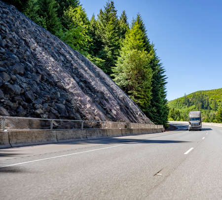 Classic gray bonnet powerful big rig long haul industrial semi truck tractor transporting commercial cargo in dry van semi trailer running uphill on the winding mountain road with rocks and forest