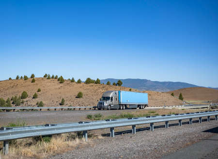 Gray bonnet big rig long haul industrial semi truck tractor transporting commercial cargo in dry van semi trailer running on the divided road across plain prairie with mountains on the horizon Stock fotó