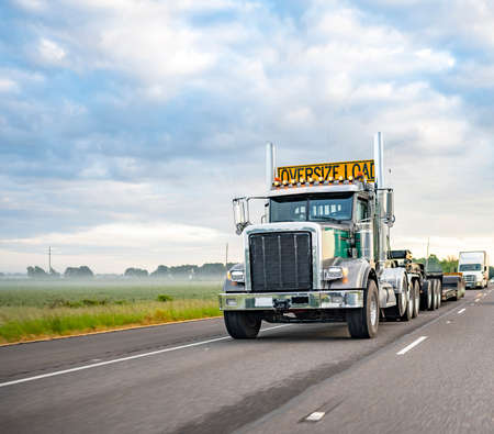 American idol green classic day cab big rig semi truck with turned on light and chrome parts and oversize load sign o the roof transporting step down semi trailer driving on the one way highway road