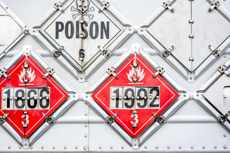 Set of the frames on the side of the semi trailer for a show information safety signs warning about the carriage of flammable or explosive or poisonous goods during semi truck transporting it