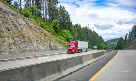 Red big rig long haul industrial semi truck tractor transporting commercial cargo in dry van semi trailer running for delivery on the summer Oregon mountain road with green trees on the hills Stock fotó