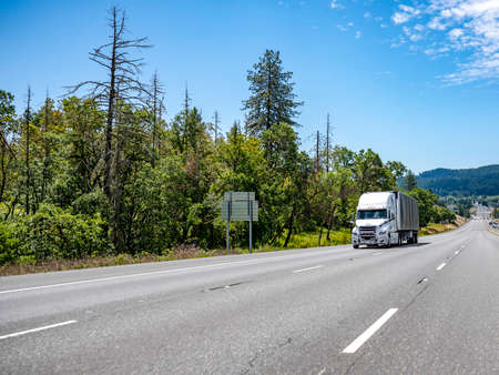 White big rig long haul day cab semi truck transporting commercial cargo in tented black dry van semi trailer with front wall spoiler running on one way highway road with trees and hill on background