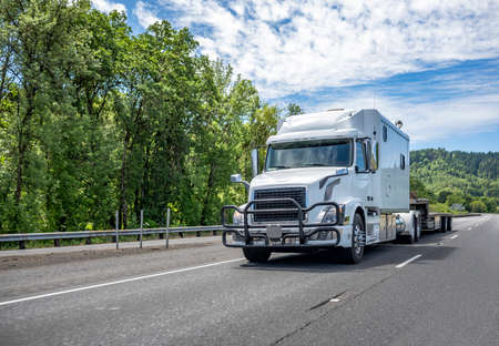 Classic white powerful big rig industrial semi truck tractor with long cab for comfort transporting empty step down semi trailer running on the divided mountain highway road with green trees