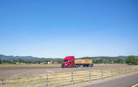 Red big rig American semi truck with high cab for comfortable long haul freight transporting lumber wood cargo on flat bed semi trailer driving on the green highway road with forest on the hills