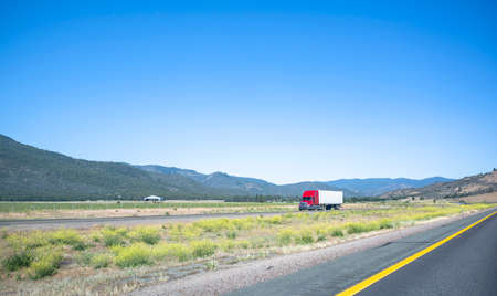 Red bonnet big rig long haul industrial semi truck tractor transporting commercial cargo in dry van semi trailer running on the divided road across plain prairie with mountains on the horizon