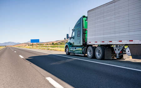 Green industrial long haul Big rig bonnet semi truck with high cab transporting frozen commercial cargo in refrigerator semi trailer running for delivery on wide multiline highway road in California Stock fotó