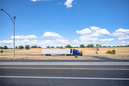 Blue industrial long haul Big rig bonnet semi truck with high cab transporting frozen commercial cargo in refrigerator semi trailer running on the local road along the highway in California