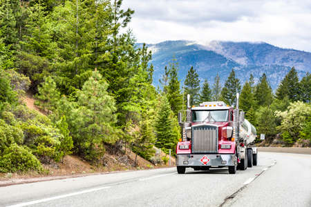 Classic red powerful big rig low profile industrial semi truck tractor transporting liquid commercial cargo in shiny armored tank semi trailer running on the winding mountain road with green forest Stock fotó