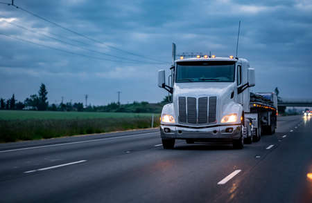 White classic big rig American semi truck with turned on lights and low profile cabin transporting covered cargo on flat bed semi trailer driving on the twilight highway road with stormy clouds sky Stock fotó