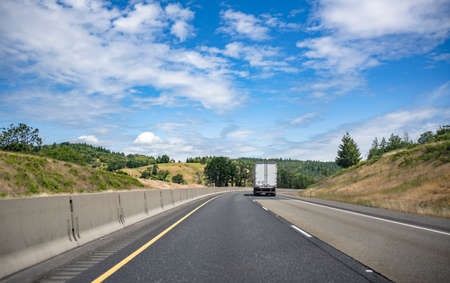 Big rig long haul industrial semi truck tractor transporting commercial cargo in dry van semi trailer running for delivery on the summer Oregon mountain road with green trees on the hills