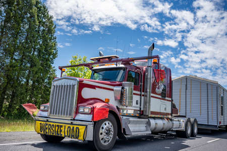 Specially equipped American idol red classic big rig semi truck with chrome parts and oversize load sign on the front transporting manufactory house  on step down semi trailer driving on highway road