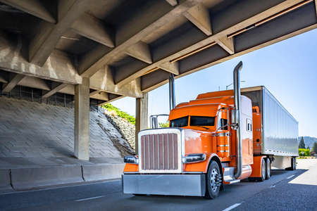 Orange Big rig long haul industrial semi truck tractor with chrome accessories transporting commercial cargo in dry van semi trailer running for delivery on the summer highway road under the bridge Stock fotó