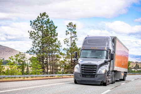 Gray big rig long haul industrial semi truck tractor transporting commercial cargo in dry van semi trailer running for delivery on the summer highway road with metal fence and trees in California