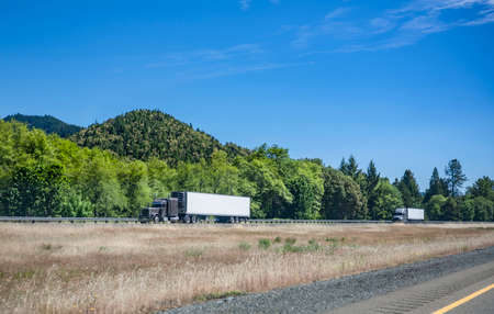 Team of two gray big rig semi trucks transporting commercial cargo in refrigerated semi trailers running in convoy on the one way highway road with grass dividing line and forest on the hills