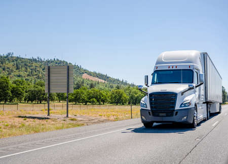 White big rig long haul industrial semi truck tractor transporting commercial cargo in dry van semi trailer running for delivery on the summer highway road along the orchards in California