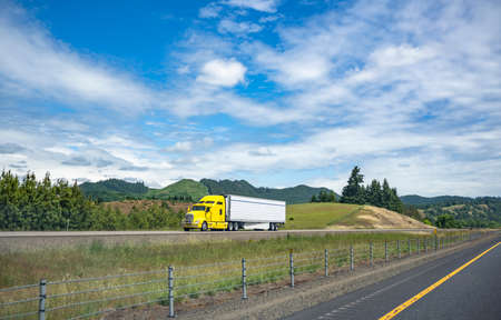 Bright yellow stylish industrial grade long haul Big rig bonnet semi truck transporting frozen commercial cargo in refrigerator semi trailer running for delivery on the one way multiline highway road