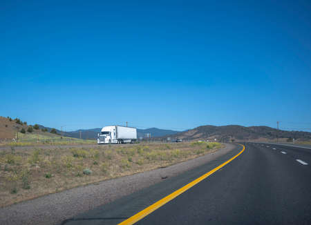 Classic white big rig semi truck with high long haul cabin transporting frozen commercial cargo in refrigerated semi trailer running on the winding divided mountain road with trees on the hillside