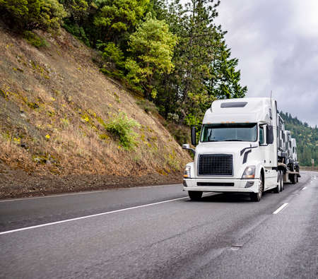 Classic white powerful big rig industrial semi truck tractor transporting fastened mobil homes on step down semi trailer running on the divided mountain highway road around mountain cliff with trees Stock fotó
