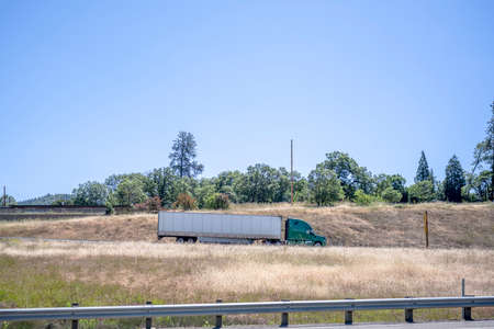 Green big rig long haul industrial semi truck tractor transporting commercial cargo in dry van semi trailer running for delivery on the road between two level hills along the highway in California