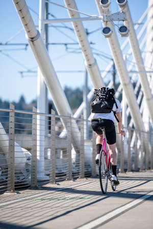 A man on a bike pedals a bicycle on a dedicated path for cyclists on the Tilikum Crossing bridge preferring an active healthy lifestyle using cycling ride and cycle as an alternative transportation
