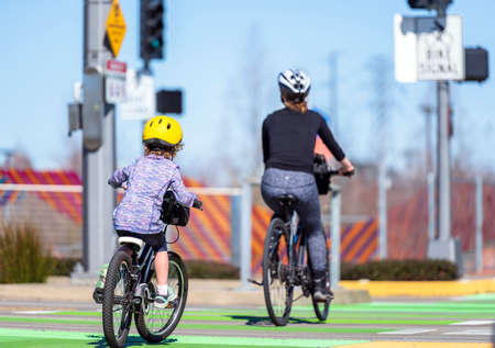 Mom and child on a bikes pedals a bicycles on the dedicated for cyclists path preferring an healthy lifestyle using cycling ride and cycle as an alternative environmentally friendly transportation