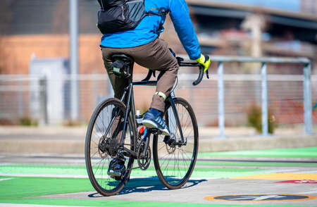 A man on a bike pedals a bicycle crosses tram tracks on a dedicated crossing for cyclists and pedestrians preferring healthy lifestyle using cycling ride and cycle as an alternative transportation