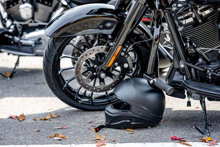 Black motorcycle safety helmet was left by a motorcyclist near the wheel of his black motorcycle with chrome details in a parking lot next to other motorcycles as a symbol of ownership and privacy