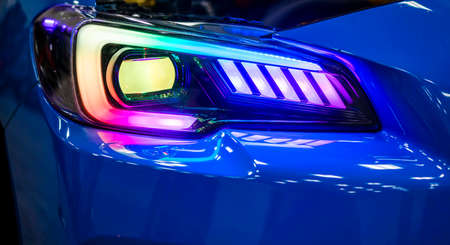 Fragment of the turned on glass headlight of the blue shiny car with neon spectrum of light reflection and glare of surrounding objects on the combined relief of the glass Stock fotó