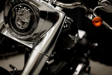 Matte chrome motorcycle with a powerful fork and stylized headlamp stands on the court in the reflection of glowing lights hiding its details in shade for riders who can appreciate its true potential Stock fotó