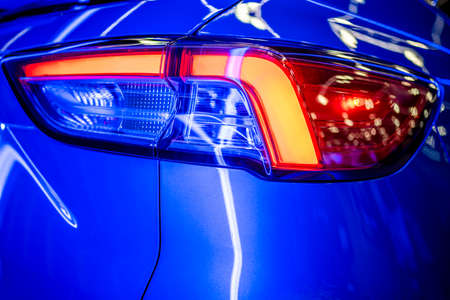 Fragment of the turned on glass taillight of the blue shiny car with neon light reflection and glare of surrounding objects on the combined relief of the glass