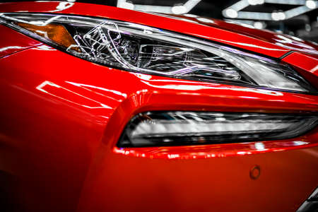 Fragment of the turned on glass headlight of the red shiny car with neon spectrum of light reflection and glare of surrounding objects on the combined relief of the glass