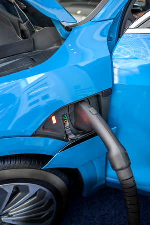 The electric car charger gun with power supply cable is inserted into the connector of the power supply charging station unit of the refueling environmentally friendly car