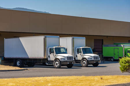 Compact industrial medium size rigs day cab semi trucks with long box trailers for local delivery and small business needs standing at warehouse dock loading commercial cargo for the next freight Stock Photo