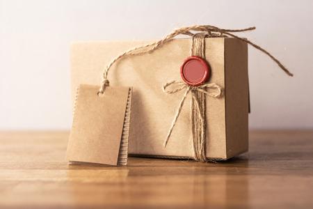 Vintage ambachtelijke kartonnen geschenkdoos met rode zegel op houten tafel Stockfoto