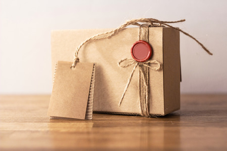 karton: Vintage rzemiosła kartonowe pudełko z czerwoną pieczęcią na drewnianym stole Zdjęcie Seryjne