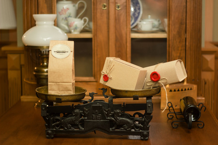 Retro craft cardboard packages with red seals on old scales Vintage shop interior. 版權商用圖片